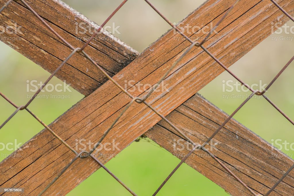 close up of chain link fence with wooden plank stock photo