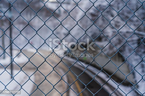 Close up of Chain linked Fence with Street in the Background