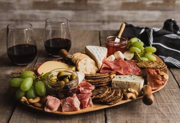 zbliżenie deski charcuterie i kieliszki wina na drewnianym stole. - deska zdjęcia i obrazy z banku zdjęć