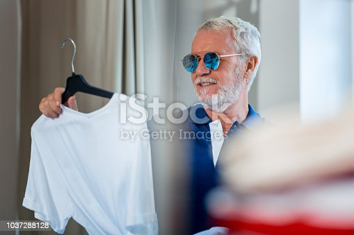 istock Close up of cheerful elderly man with T-shirt in hand 1037288128
