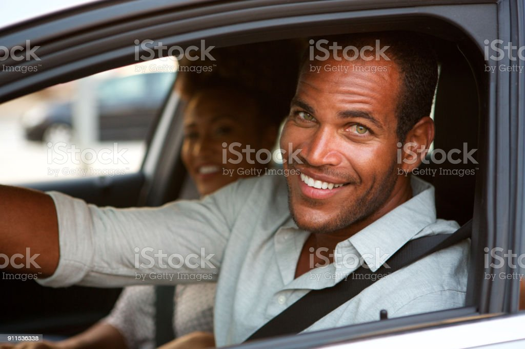 Close up of cheerful man and woman in car on road trip stock photo
