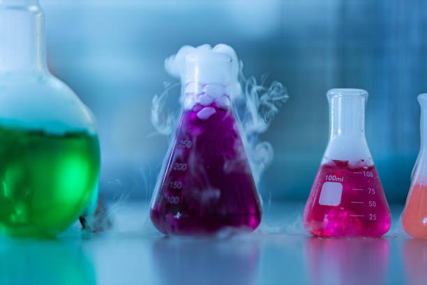 Close up of chemical reactions in beakers at laboratory. Close up of group of beakers with chemical reactions in laboratory. Copy space. Focus is on beaker with pink liquid. chemical reaction stock pictures, royalty-free photos & images
