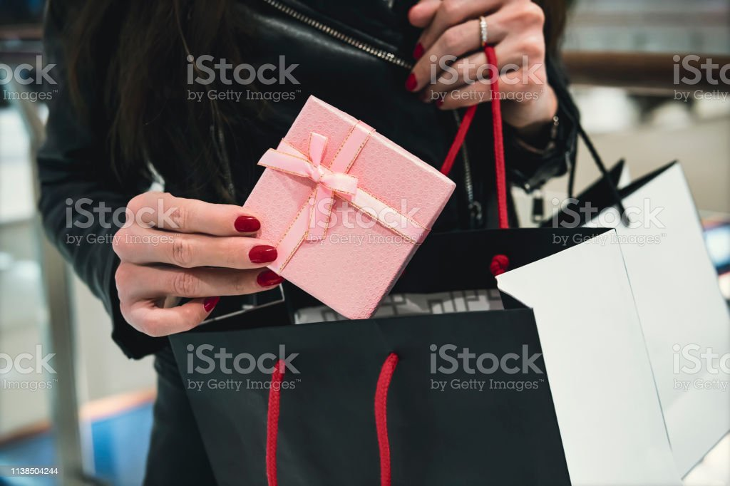 Close up of chic woman\'s hands holding decorated pink present and...