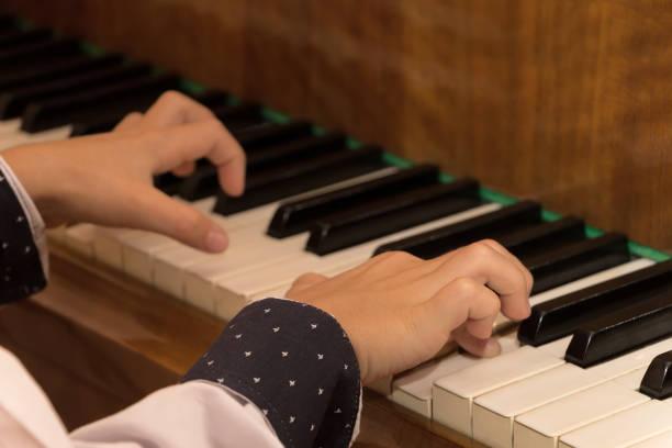 nahaufnahme der kinderhände, die klavier spielen. selektiver fokus. warmer schatten. junge finger und schöne hemd ärmel. braunes klavier mit schwarzen und weißen tasten. klavierspielen lernen an einer musikschule - one song training stock-fotos und bilder