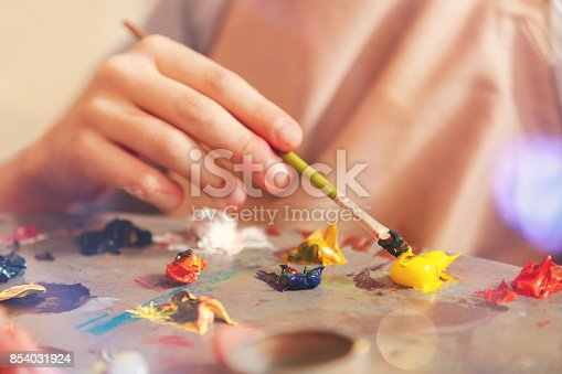 824254912 istock photo Close up of child mixing oil paints on palette 854031924