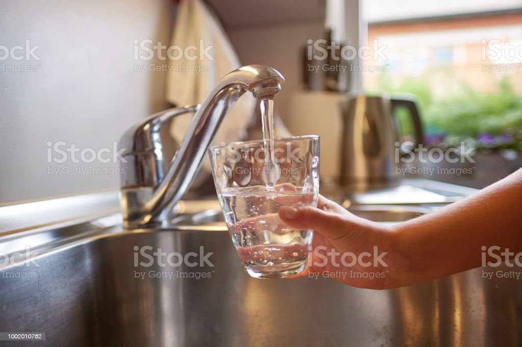 Close up of children hands, pouring glass of fresh water from tap in kitchen royalty-free stock photo
