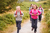 Close up of children running ahead of parents on a country path during a family vacation, front view