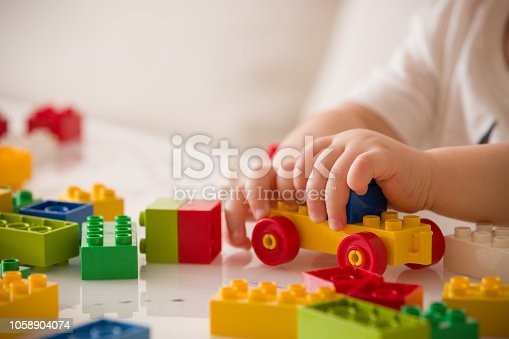 istock Close up of child's hands playing with colorful plastic bricks at the table. Toddler having fun and building out of bright constructor bricks. Early learning.  stripe background. Developing toys 1058904074