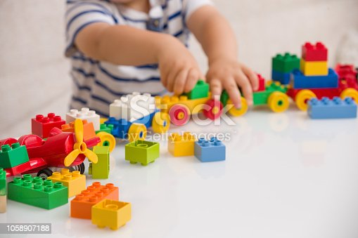 istock Close up of child's hands playing with colorful plastic bricks at the table. Toddler having fun and building out of bright constructor bricks. Early learning.  stripe background. Developing toys 1058907188