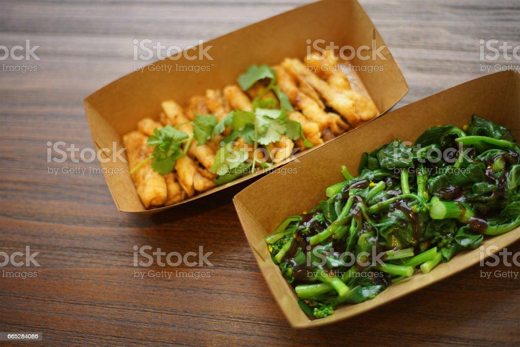 close up of chinese dishes in paper plates stock photo