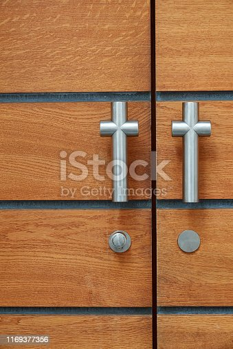 Close up of church door with two stainless steel crosses as doorknobs