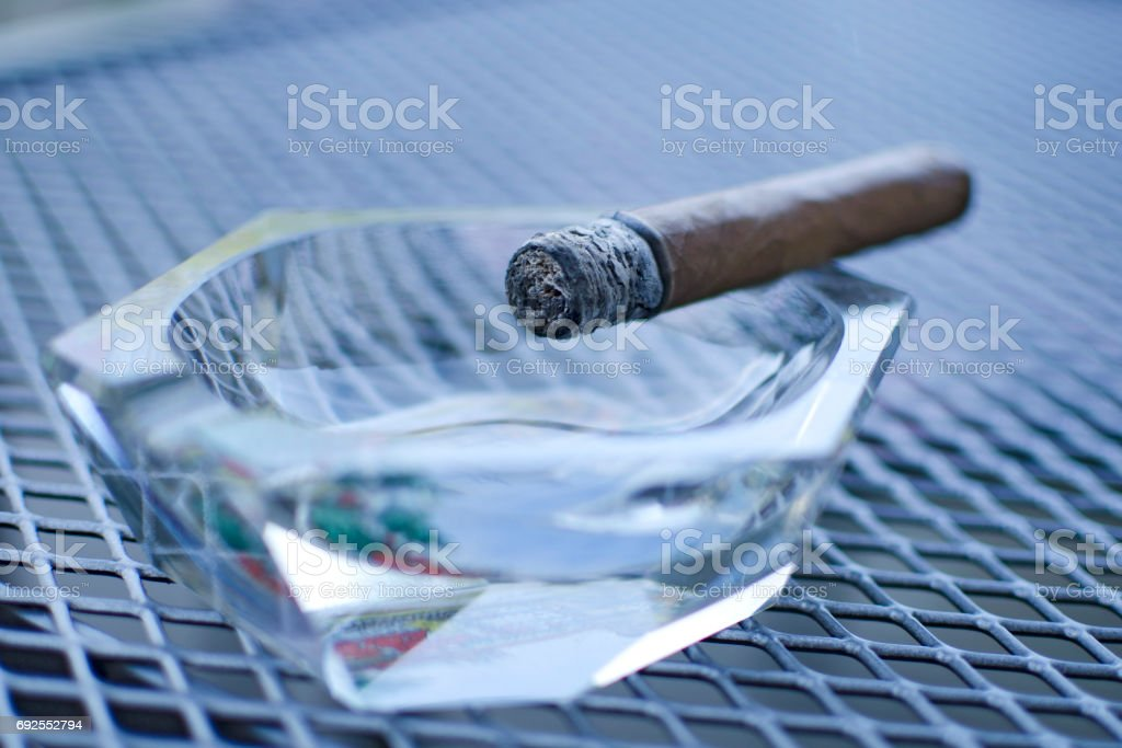 Close up of cigar with glass ashtray on the wired table stock photo