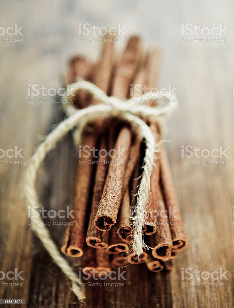Close up of cinnamon sticks tied with bow of twine on table stock photo