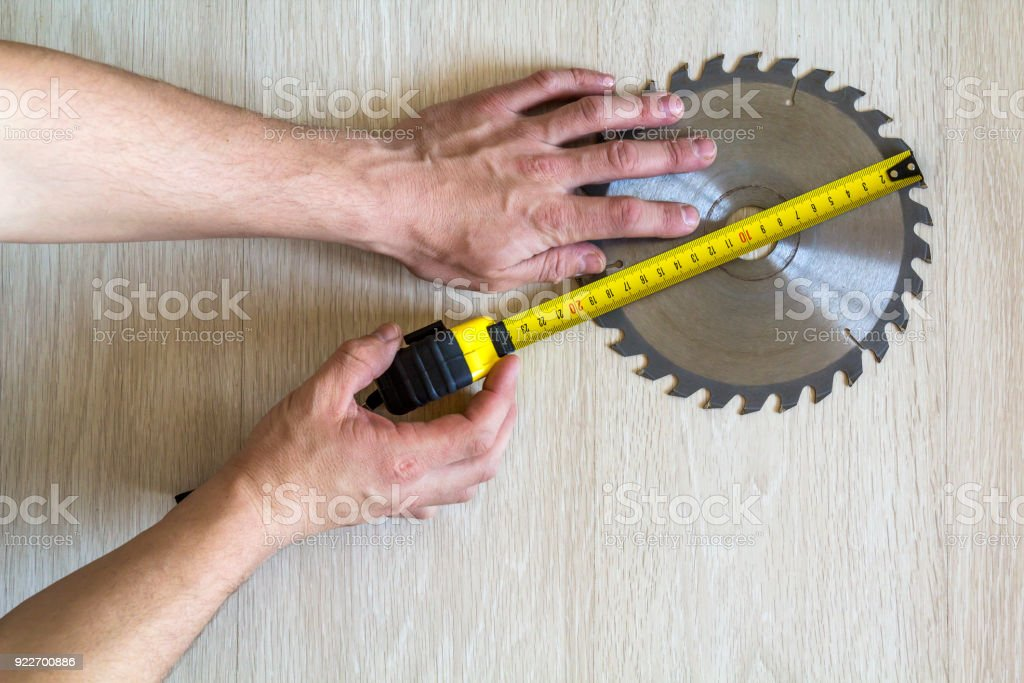 Close up of circular saw blade for wood work and worker hand with measuring tape on wooden background. Top view. stock photo