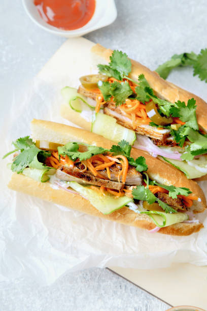 Close up of classical banh-mi sandwich with sliced grilled pork tenderloin, shredded carrots and peeled cucumbers, jalapeno peppers and cilantro on white textured background Close up of classical banh-mi sandwich with sliced grilled pork tenderloin, shredded carrots and peeled cucumbers, jalapeno peppers and cilantro on white textured background bánh mì sandwich stock pictures, royalty-free photos & images