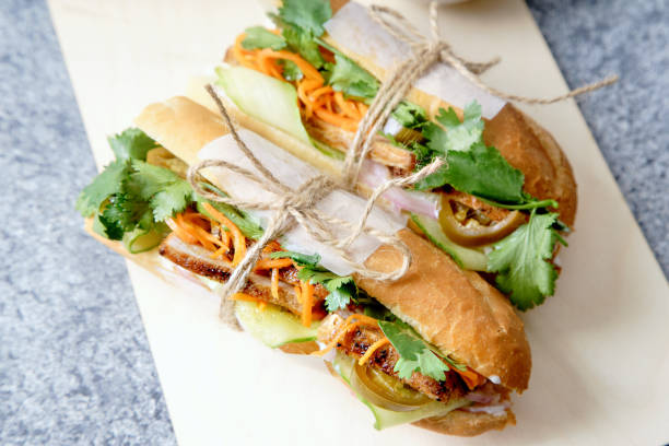 Close up of classical banh-mi sandwich with sliced grilled pork tenderloin, shredded carrots and peeled cucumbers, jalapeno peppers and cilantro Close up of classical banh-mi sandwich with sliced grilled pork tenderloin, shredded carrots and peeled cucumbers, jalapeno peppers and cilantro bánh mì sandwich stock pictures, royalty-free photos & images