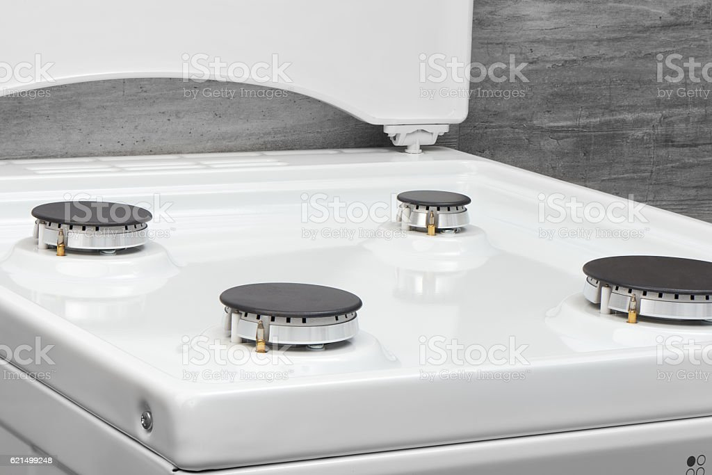 Close up of clean white kitchen gas stove on gray Lizenzfreies stock-foto