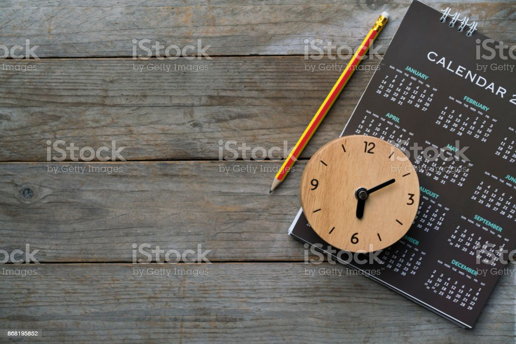 close up of clock, calendar and pencil on the table, planning for business meeting or travel planning concept stock photo