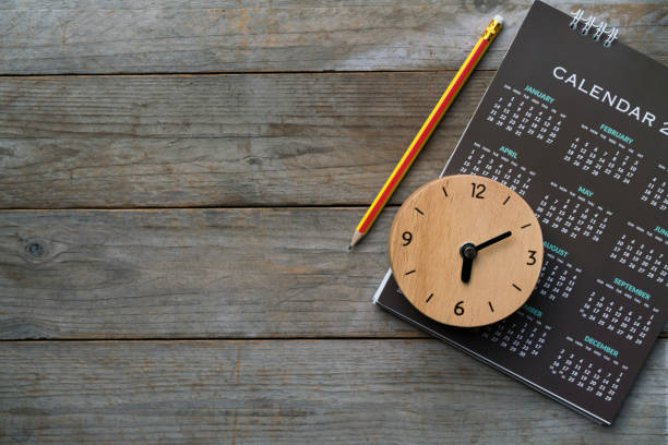close up of clock, calendar and pencil on the table, planning for business meeting or travel planning concept - calendar date stock photos and pictures
