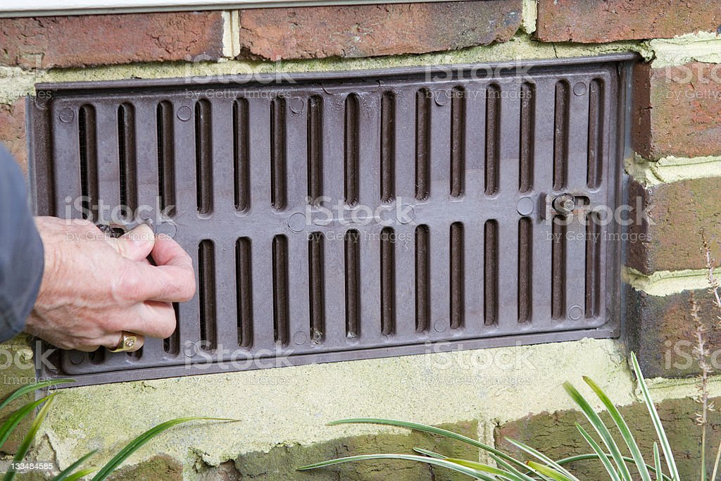 Close up of closing a foundation vent for winter. stock photo