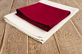 close up of cloth napkins of beige, and burgundy colors on rustic brown wooden table. Shallow depth of field.