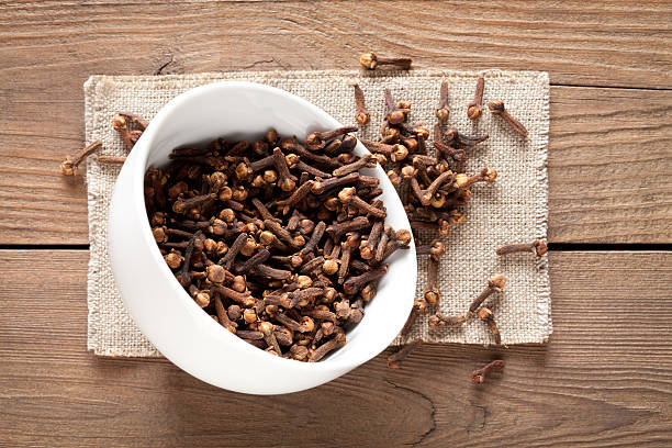 Close up of cloves in cup on wooden table Close up of cloves in cup on old wooden table. This file is cleaned and retouched. clove spice stock pictures, royalty-free photos & images