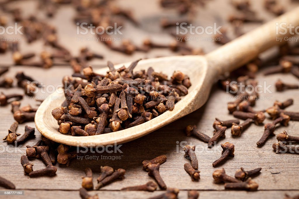 Close up of cloves in spoon on wooden table stock photo