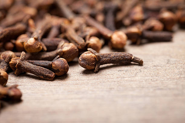 Close up of cloves on old wooden table Close up of cloves on old wooden table. On bottom right is empty space to put text or something else. This file is cleaned and retouched. clove spice stock pictures, royalty-free photos & images