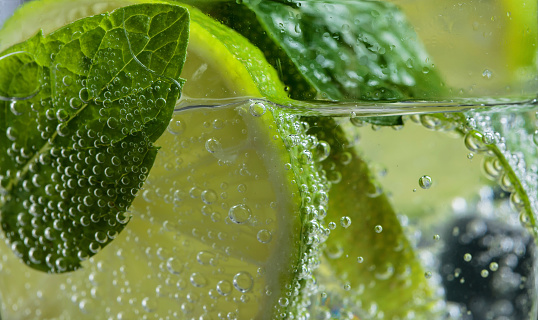 Close up of cocktail with lime , ice  and mint  .