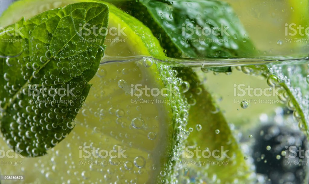 Close up of cocktail with lime , ice  and mint  . stock photo