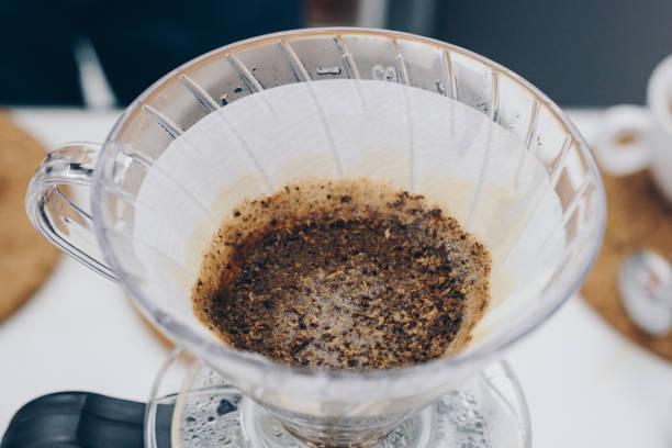 nahaufnahme des dip kaffeefilter nach barista gießt heißes wasser kaffeepulver. - kaffeepulver stock-fotos und bilder