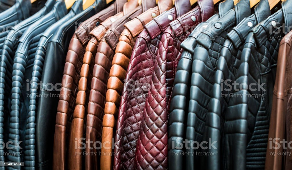 Close up of collection of handmade multi colored leather jackets hanging in a row and for sale at clothing market stock photo