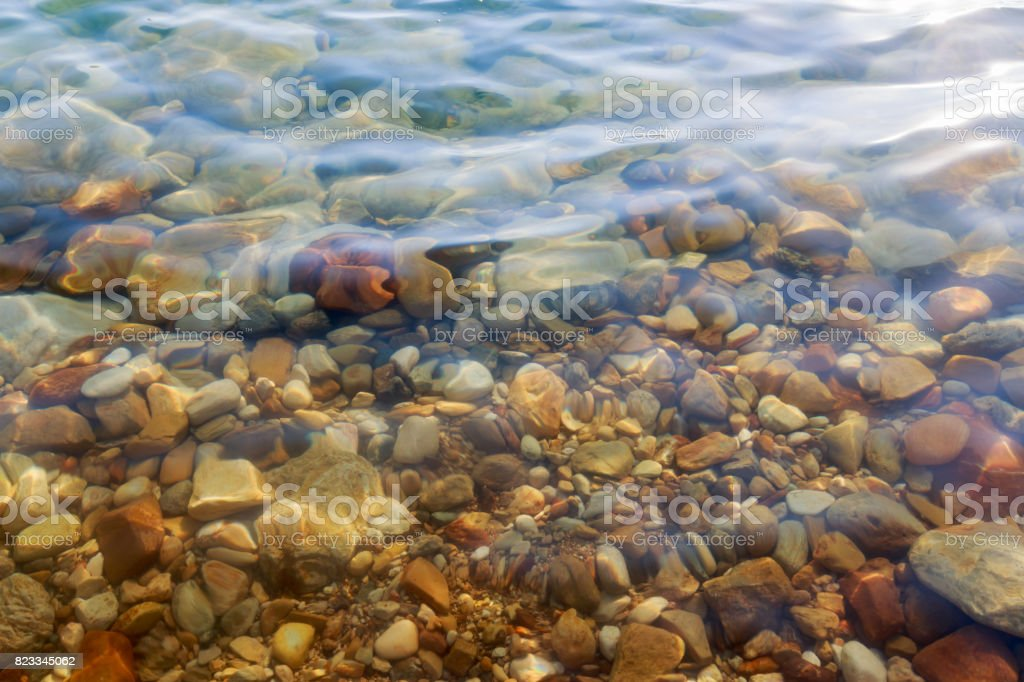 Close up of colored stones under salty water at the Dead Sea coast, Jordan. stock photo