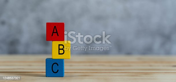 Close up of colorful A B C  letters alphabet on cube blocks on wooden background .Business concept for choose backup plan or children kids toy for play or learning of preschool. Copy space for text.