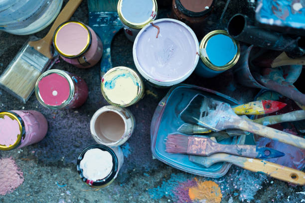 close up of colorful bunch of brushes and paint on floor with color stains outdoor, used to make urban art or diy painting decorations stock photo