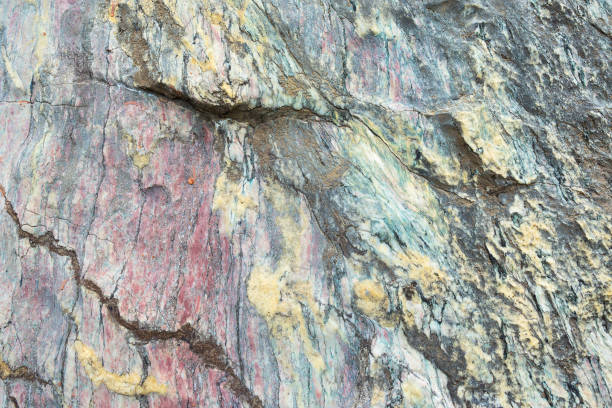 Close up of colorful rock surface, natural background, pattern and texture. Metamorphic white quartzite folded and fractured together with red coarse sandstone, due to the power of geologic crustal movement. stock photo
