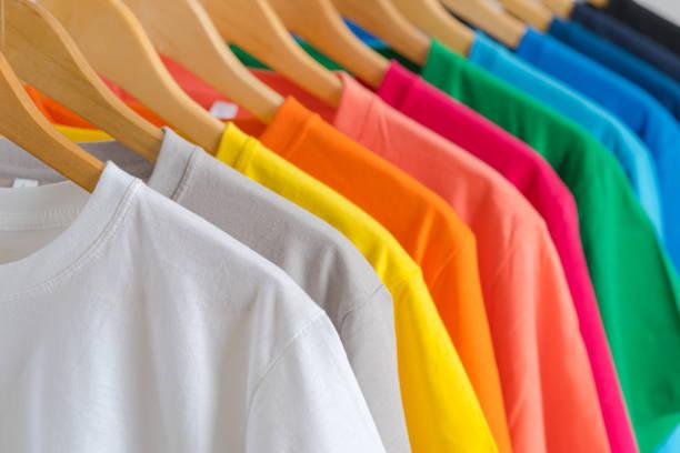zbliżenie kolorowych t-shirtów na wieszakach, tło odzieży - odzież zdjęcia i obrazy z banku zdjęć