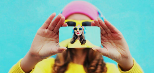 Close up of colorful woman stretching her hands taking selfie picture by phone over blue background stock photo