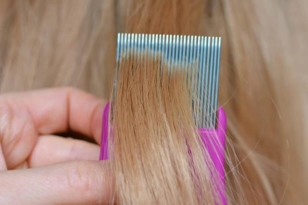 nahaufnahme von kämmenden blonden haaren mit einem läusekamm - kopfläuse was tun stock-fotos und bilder
