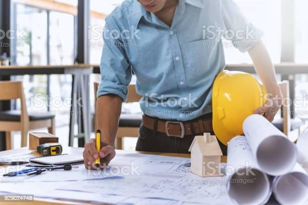 Nahaufnahme Von Konzentrierte Männliche Ingenieur Drawing Hand An Architektonische Projekt Auf Baustelle Am Schreibtisch Im Büro Arbeiten Stockfoto und mehr Bilder von Arbeiten