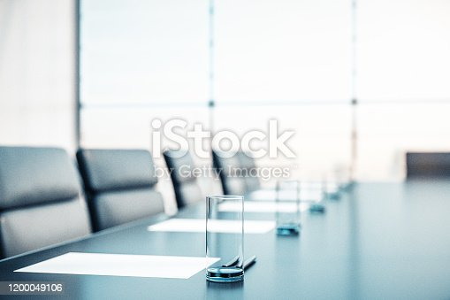 Close up of conference room with glasses of water on the table with papers, armchairs and a large window. 3D Rendering