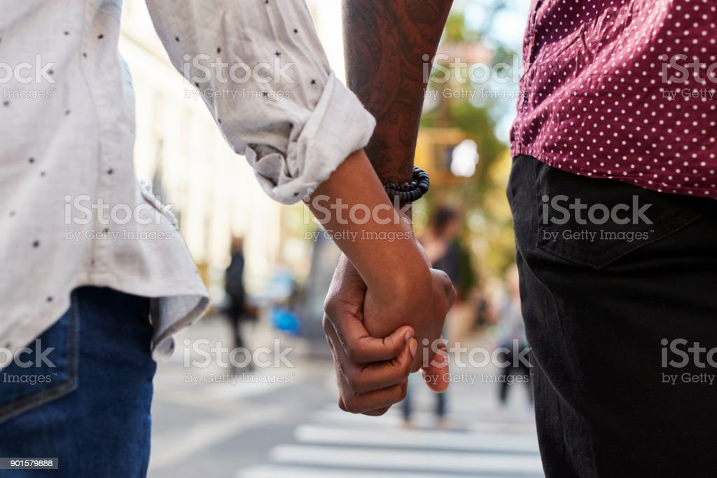 Close Up Of Couple Holding Hands On Urban Street stock photo