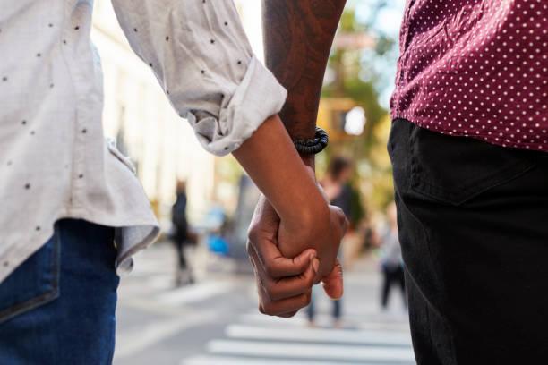 De cerca de pareja cogidos de la mano en la calle urbanita - foto de stock