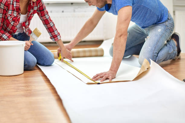 close up of couple measuring wallpaper stock photo