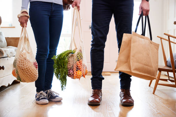 close up of couple returning home from shopping trip carrying groceries in plastic free bags - grocery home foto e immagini stock