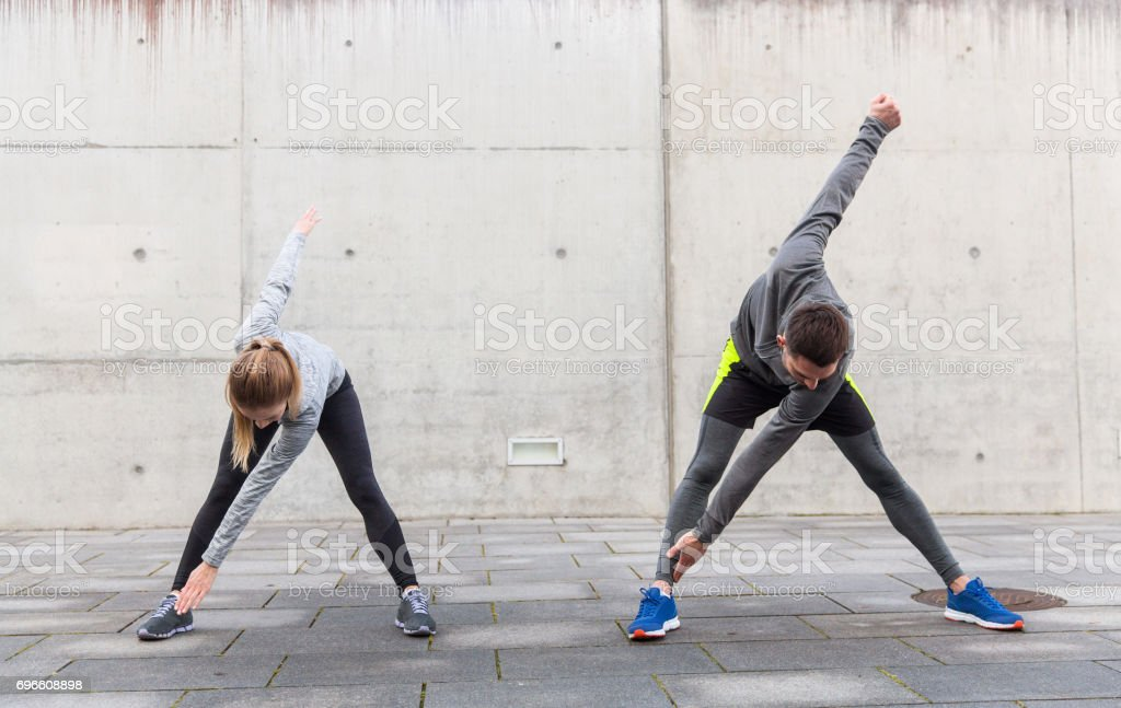 close up of couple stretching on city street stock photo