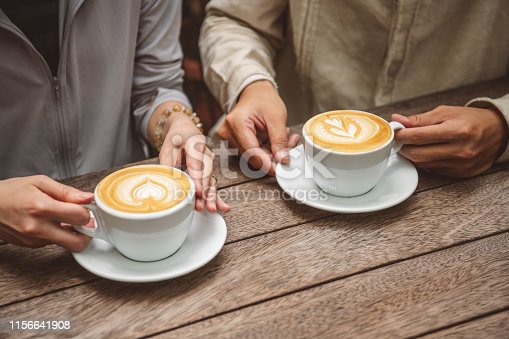 Close up of two people sitting at wooden table holding cups of coffee, hands, romance, dating