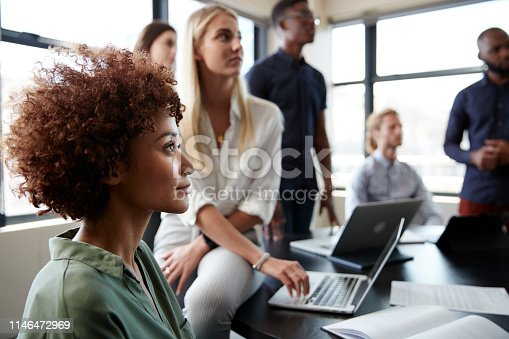 Close up of creative business colleagues listening to an informal presentation in a meeting room