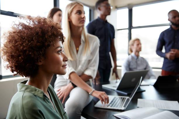zbliżenie kreatywnych kolegów biznesowych słuchających nieformalnej prezentacji w sali konferencyjnej - selektywna głębia ostrości zdjęcia i obrazy z banku zdjęć