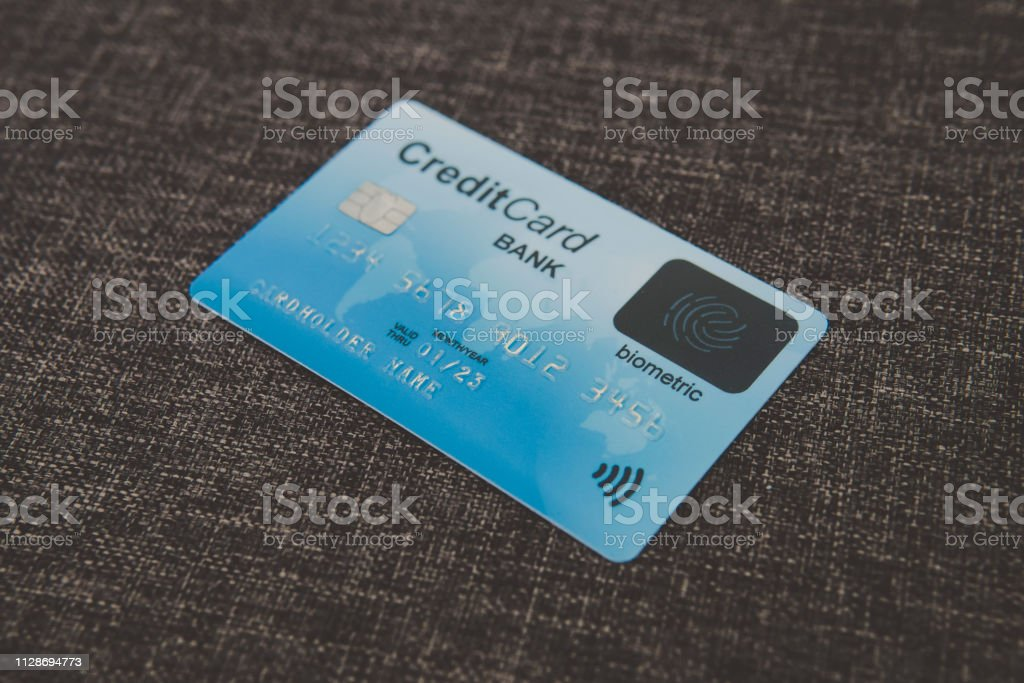 Close up of credit biometric card belonging to abstract cardholder lying on coarse fabric. E-shopping using advantages of fingerprint scanning. Simplicity and security of biometrics in banking. Chip. stock photo